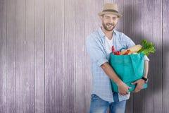 Imagem composta do retrato do homem que guarda o saco com vegetais Imagens de Stock