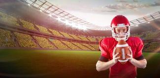 Imagem composta do retrato do jogador de futebol americano focalizado que guarda o futebol Imagem de Stock