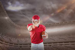 Imagem composta do retrato do jogador de futebol americano que guarda o futebol e que aponta à câmera Fotos de Stock Royalty Free
