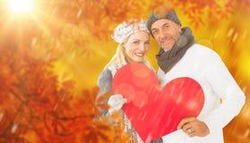 Imagem composta do retrato dos pares felizes que guardam o coração fotos de stock royalty free