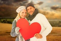 Imagem composta do retrato dos pares felizes que guardam o coração fotografia de stock