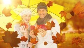 Imagem composta do retrato dos pares que guardam as folhas de outono ao estar sob o guarda-chuva amarelo imagem de stock royalty free