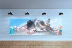 Imagem composta do underwater de beijo dos pares bonitos na piscina imagens de stock