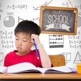Imagem composta dos alunos bonitos que escrevem na mesa na sala de aula imagem de stock