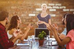 Imagem composta dos colegas que aplaudem as mãos em uma reunião fotografia de stock