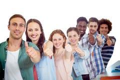 Imagem composta dos estudantes da forma que mostram os polegares acima Fotografia de Stock Royalty Free