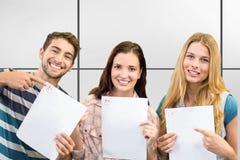 Imagem composta dos estudantes de sorriso que mostram seus exames fotografia de stock