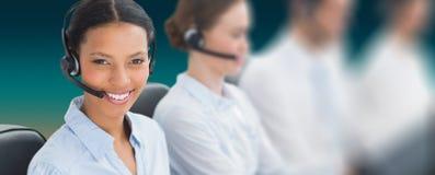 Imagem composta dos executivos com auriculares usando computadores fotografia de stock royalty free
