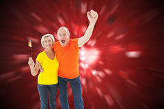 Imagem composta dos pares alemães felizes que cheering na câmera fotos de stock royalty free