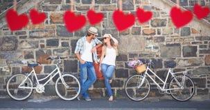 Imagem composta dos pares atrativos que estão com bicicletas Fotografia de Stock