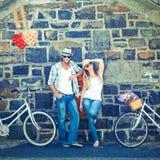 Imagem composta dos pares atrativos que estão com bicicletas Fotografia de Stock Royalty Free