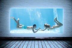 Imagem composta dos pares bonitos que mantêm as mãos subaquáticas na piscina fotos de stock royalty free