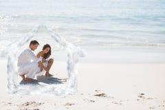Imagem composta dos pares bonitos que tiram um coração na areia Fotos de Stock Royalty Free