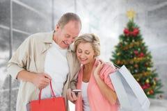 Imagem composta dos pares com sacos de compras e smartphone fotos de stock