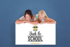Imagem composta dos pares de sorriso bonitos que inclinam-se em um whiteboard Fotografia de Stock Royalty Free