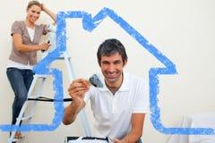 Imagem composta dos pares de sorriso que pintam uma parede Fotografia de Stock Royalty Free