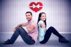 Imagem composta dos pares de sorriso que sentam-se mostrando os polegares acima Imagens de Stock