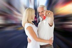 Imagem composta dos pares felizes que mostram sua chave da casa nova Fotografia de Stock Royalty Free