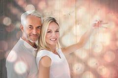 Imagem composta dos pares felizes que mostram sua chave da casa nova Imagens de Stock