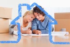 Imagem composta dos pares felizes que organizam sua casa nova Fotos de Stock Royalty Free
