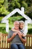Imagem composta dos pares maduros que abraçam no jardim Imagens de Stock
