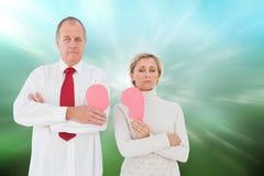 Imagem composta dos pares mais velhos que estão guardando o coração cor-de-rosa quebrado Imagens de Stock Royalty Free