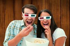 Imagem composta dos pares novos atrativos que olham um filme 3d Fotografia de Stock