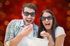 Imagem composta dos pares novos atrativos que olham um filme 3d Imagens de Stock