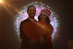 A imagem composta dos pares novos felizes que guardam o coração dá forma ao papel Imagens de Stock Royalty Free