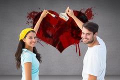 Imagem composta dos pares novos felizes que pintam junto Foto de Stock