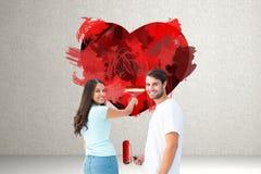 Imagem composta dos pares novos felizes que pintam junto Fotografia de Stock