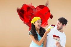 Imagem composta dos pares novos felizes que pintam junto e que riem Imagem de Stock Royalty Free