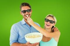 Imagem composta dos pares novos felizes que vestem os vidros 3d que comem a pipoca Imagem de Stock Royalty Free