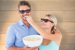 Imagem composta dos pares novos felizes que vestem os vidros 3d que comem a pipoca Foto de Stock Royalty Free