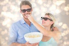 Imagem composta dos pares novos felizes que vestem os vidros 3d que comem a pipoca Imagens de Stock Royalty Free