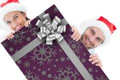 Imagem composta dos pares novos festivos que sorriem na câmera Imagens de Stock
