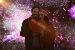 A imagem composta dos pares novos que guardam o coração dá forma ao papel Foto de Stock