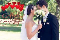 Imagem composta dos pares que beijam atrás do ramalhete no jardim Imagens de Stock