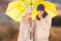 Imagem composta dos pares que espirram no tecido ao estar sob o guarda-chuva imagem de stock