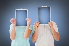 Imagem composta dos pares que guardam excedente de papel suas caras Fotos de Stock