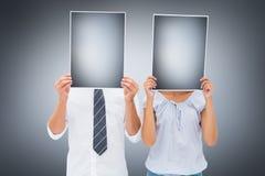Imagem composta dos pares que guardam excedente de papel suas caras Fotografia de Stock