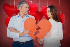 Imagem composta dos pares que guardam o papel 3D da forma do coração quebrado Foto de Stock