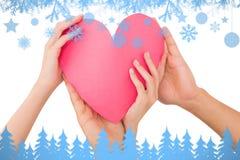 Imagem composta dos pares que guardam um coração de papel Foto de Stock Royalty Free