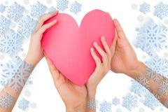Imagem composta dos pares que guardam um coração de papel Imagens de Stock