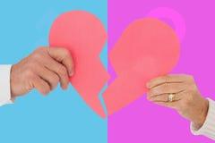 Imagem composta dos pares que guardam um coração de papel quebrado Imagens de Stock Royalty Free