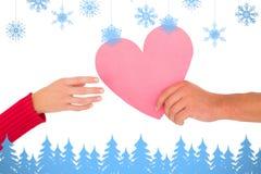 Imagem composta dos pares que passam um coração de papel Foto de Stock