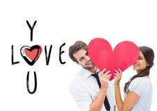 Imagem composta dos pares que sorriem na câmera que guarda um coração Foto de Stock