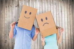 Imagem composta dos pares que vestem caixas tristes da cara em suas cabeças Fotografia de Stock Royalty Free