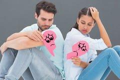 Imagem composta dos pares tristes que sentam-se guardando duas metades de coração quebrado Fotografia de Stock Royalty Free