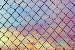 Imagem conceptual do céu crepuscular com efeito do tom pastel claro e da cerca de fio de aço da malha imagem de stock